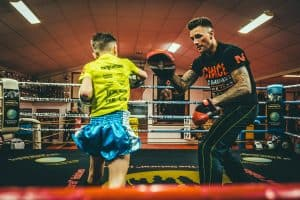 A photo of Nieky Holzken holding pads for a young fighter in the ring at one of his Dutch Kickboxing gyms
