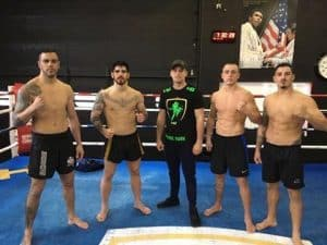 A photo of Nick Hemmers with a group of his fighters in the ring at Hemmers Gym in Breda