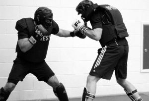 Two Martial Arts practitioners training self-defence by sparring in body armour