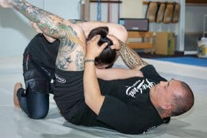 A photo of Enson Inoue finishing the triangle in MMA as a demonstration for the Warrior Collective