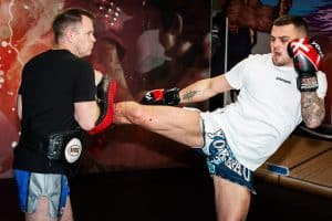 A photo of Richard Smith from Muay Thai 101 - A Framework for Developing Fighters as he holds the pads in training