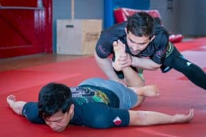A photo of Lyubo Kumbarov doing post training massage to aid the development of flexibility in grappling