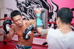 A photo of Genji Umeno demonstrating Muay Thai Elbow Techniques on Thai Pads