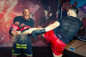 A photo of Vos Gym K-1 Kickboxing Coach Ivan Hippolyte holding Thai Pads