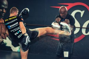 A photo of Ernesto Hoost training world level dutch kickboxing with one of his fighters